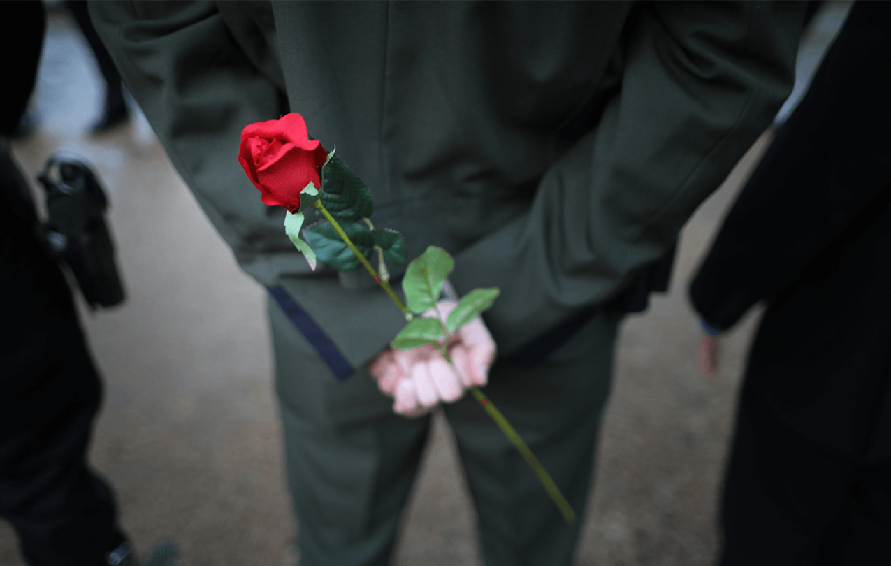 Three law enforcement officers stand next to one another with hands clasped behind their backs. One is holding a single rose.